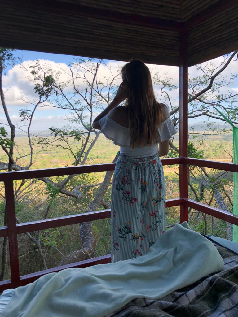 girl looking at the view from a treehouse nicaragua